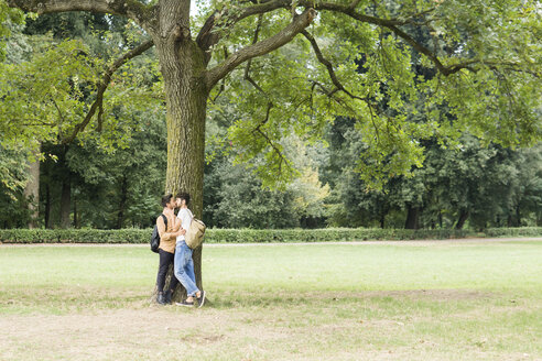 Kissing young gay couple leaning against tree in city park - FBAF00063