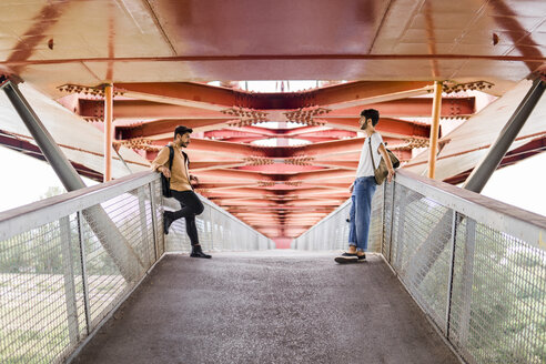 Young gay couple standing on modern footbridge looking at each other - FBAF00069