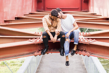Young gay couple in love sitting on steel girders of a footbridge - FBAF00075