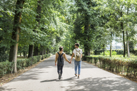 Back view of young gay couple with backpacks walking hand in hand on a road - FBAF00084
