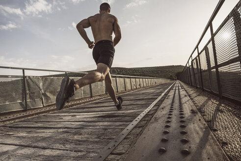 Rear view of young shirtless man running on bridge - JASF01959