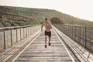 Young shirtless man running on bridge - JASF01962