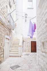 Italy, Puglia, Polognano a Mare, narrow alley and staircase at historic old town - FLMF00040