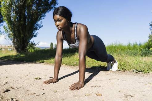 Young athlete doing push ups on the dirt track - GIOF04447