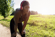 Young athlete in nature, listening music with headphones, preparing for training - GIOF04456