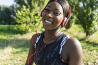 Young athlete in nature, listening music with headphones - GIOF04459