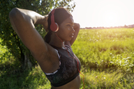 Young athlete in nature, listening music with headphones - GIOF04468