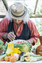 Senior man working on a watermelon with carving tool - FBAF00111