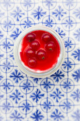 Greek yogurt with red currant sauce on blue patterned tiles - LVF07447