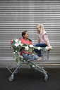 Two smiling girls crouching in shopping cart decorated with artificial flowers - PSTF00175