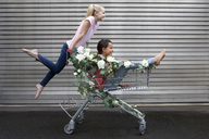 Two girls playing with shopping cart decorated with white artificial flowers - PSTF00178