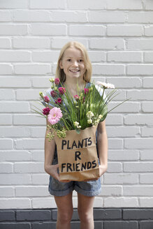 Portrait of smiling girl with paper bag of flowers - PSTF00184