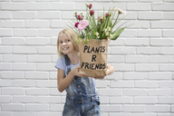 Portrait of smiling girl holding paper bag with flowers - PSTF00187