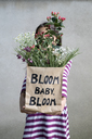 Girl holding paper bag with flowers - PSTF00190