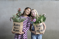 Portrait of two smiling girls holding paper bags with flowers - PSTF00193