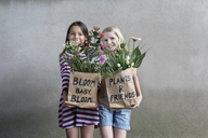 Portrait of two smiling girls standing side by side offering paper bags with flowers - PSTF00196