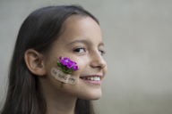 Portrait of smiling girl with flower head on her cheek - PSTF00199