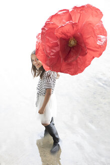 Portrait of smiling girl standing in a lake with oversized red artificial flower - PSTF00205