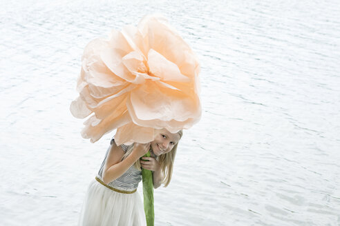 Portrait of smiling blond girl standing in a lake holding oversized artificial flower - PSTF00208