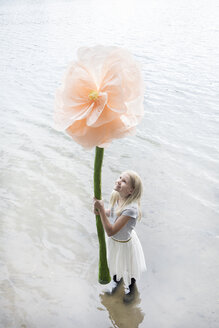 Smiling blond girl standing in a lake holding oversized artificial flower - PSTF00211