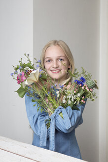 Portrait of smiling blond girl with bunches of flowers in sleeves of her dress - PSTF00217