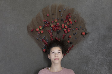 Portrait of girl lying on floor and fruits on hair - PSTF00220