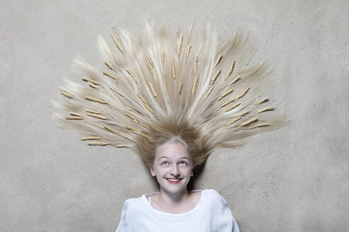 Portrait of smiling girl lying on floor with ears of wheat on hair looking up - PSTF00223