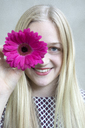 Portrait of smiling blond girl with flower head of pink Gerbera - PSTF00232