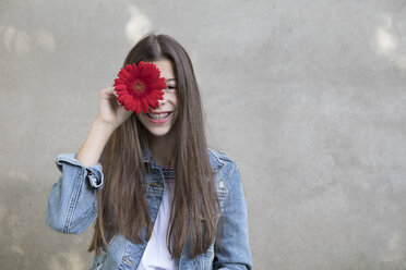 Portrait of laughing girl with flower head of red Gerbera - PSTF00235