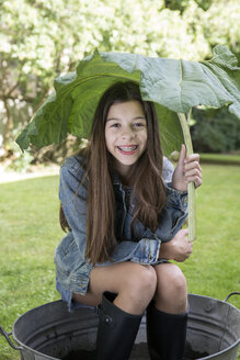Portrait of smiling girl under big leaf sitting in tub in the garden - PSTF00238
