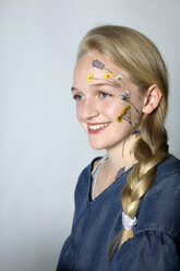 Portrait of smiling blond girl with tattoo of pressed flowers on her face - PSTF00241
