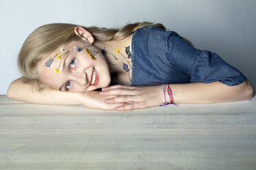 Portrait of smiling blond girl with tattoo of pressed flowers on her face - PSTF00244