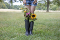 Legs of girl standing on a meadow with bunches of flowers in her rubber boots - PSTF00253