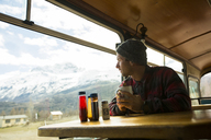 Traveler enjoying coffee on train and looking at view of mountains, Patagonia, Chile - AURF05643