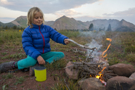 Young girl starting campfire along Colorado Trail near Trout Lake and Kennebac Pass in San Juan National Forest - AURF05769