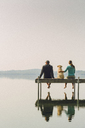 Woman, dog and man relaxing on the end of long lake dock. - AURF05775