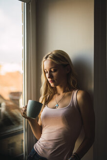 Blond young woman holding coffee mug at the window - KKAF01982