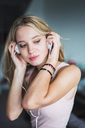 Blond young woman listening to music with headphones - KKAF02003