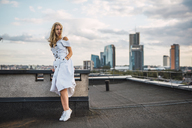 Blond young woman standing on roof terrace wearing white dress - KKAF02012