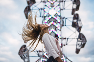 Long-haired young woman shaking her hair on a funfair - KKAF02015