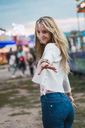 Smiling young woman on a funfair reaching out her hand - KKAF02021