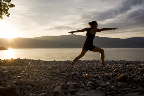 Young woman doing yoga at the stony beach at sunset, Warrior pose - JESF00173