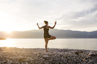 Young woman doing yoga on a stony beach at sunset, tree position - JESF00176