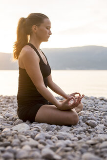 Young woman doing yoga at the stony beach in the evening, meditation - JESF00179
