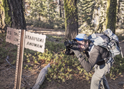 A young man photographs the light streaming through a trail sign while hiking in Yosemite National Park, California - AURF05856