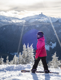 A Female Snowboarder Takes A Break And Looks Out At The View Of Black Tusk From Whistler Blackcomb Ski Resort - AURF05877