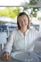 Portrait of smiling woman at an outdoor restaurant - PSIF00076