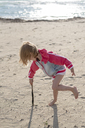 Greece, Parga, little girl playing with a stick on the beach - PSIF00079