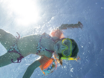 Little girl wearing diving goggles swimming in water - PSIF00091