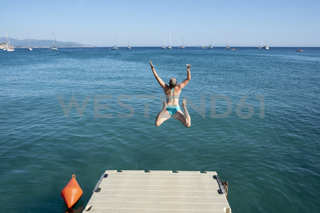 Greece, Parga, carefree woman jumping from jetty into the sea - PSIF00103 - Petra Silie/Westend61